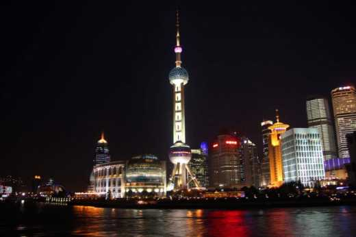 View of the Pearl Tower and surrounding buildings on the Shanghai river cruise at night.