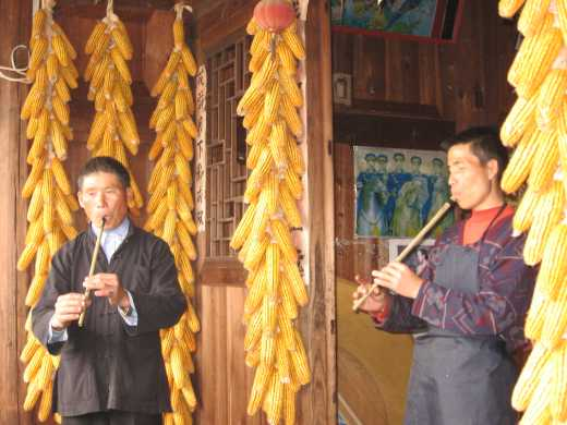 Two men playing reed flutes in Qingman Miao village